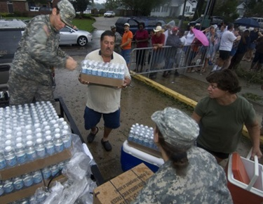 Army National Guard Spc. Jacquelyn Smith and Sgt. Paul Sehlinger of 1084 Transportation Division, Slidell, La. hands out bottles of water to local citizens affected by Hurricane Gustav.