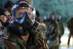 Photo of service member in uniform with gas mask on for training