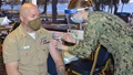 Military health personnel wearing a face mask and a face shield giving the COVID-19 vaccine