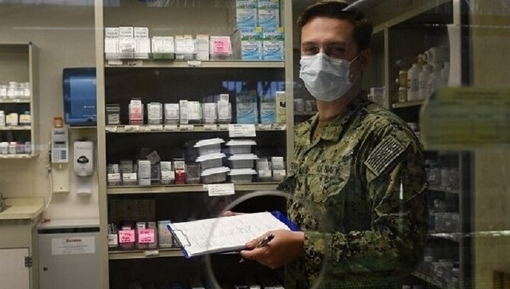 Soldier wearing mask, marking items off in supply room