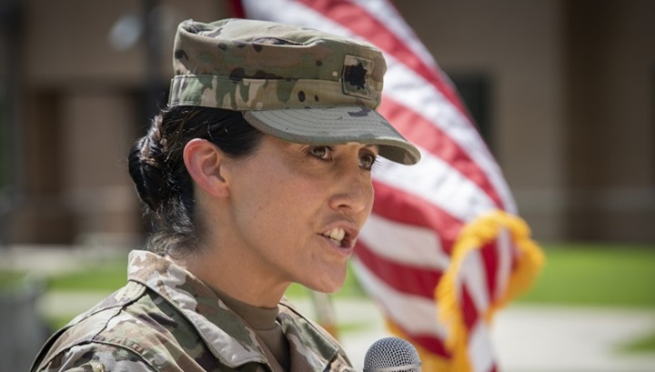 Soldier in front of flag speaking into microphone