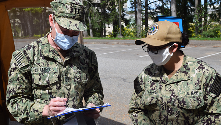Masked Navy members consult clipboard.