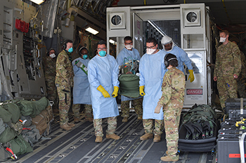 Military medical personnel, wearing masks and gloves, loading a COVID-19 patient into an isolated containment chamber