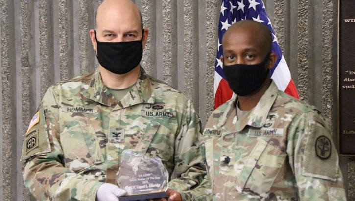 Two military personnel, wearing masks, holding a crystal award