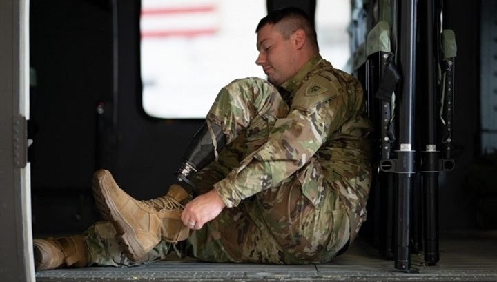 Soldier with leg prosthesis putting on his shoe.