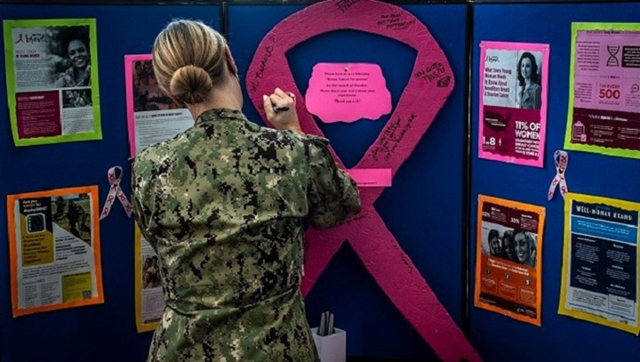 Soldier standing in front of a colorful display with pink ribbon