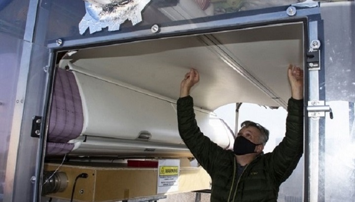 Man wearing mask, looking at ceiling of an airplane