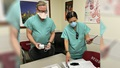 Two medical personnel, wearing masks, looking at the contents of a home-based COVID treatment kit