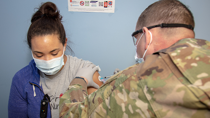 Soldier gives a nurse a vaccine in her left arm