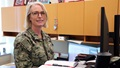 Military officer sitting at her desk and smiling