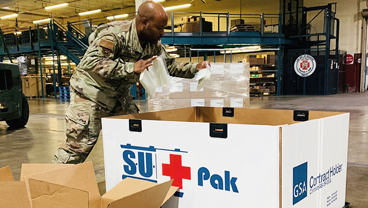 Military member in warehouse, packing a large box