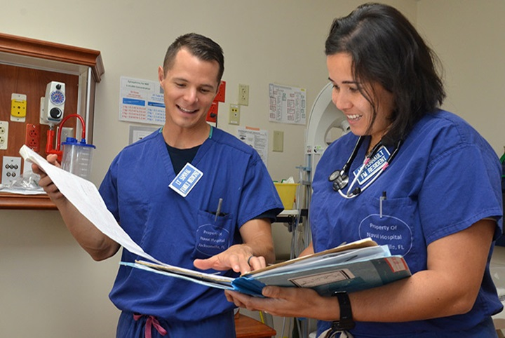 Naval Hospital Jacksonville physicians Lt. Catherine Perrault, right, and Lt. Joseph Sapoval review patient charts at the hospital's labor and delivery unit. Perrault, from Orlando, Florida, rendered aid at the scene of an accident involving a train and a school bus on Sept. 27, 2018. Perrault recently returned from a deployment to the Middle East where she served as the general medical officer aboard the amphibious assault ship USS Iwo Jima (LPH 2). During the deployment, she provided routine, acute, and critical care. (U.S. Navy photo by Jacob Sippel/Released)