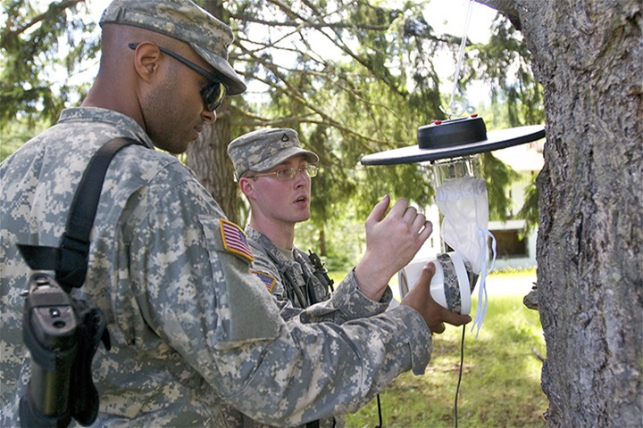 Spc. Joshua Jones, left, and Pfc. Richard Bower, both preventive medicine specialists, 227th Preventive Medicine Detachment, 62nd Medical Brigade, check an insect trap during a field training exercise on Joint Base Lewis-McChord, June 20. The 227th PMD notionally deployed to Guiria, Venezuela, where a tropical storm caused floods and presented a real world concern for mosquitos, which are known to spawn in stagnant water and cause widespread vector borne illnesses such as malaria, yellow fever and dengue fever.  Photo by Sgt. Sarah Enos 5th Mobile Public Affairs Detachment