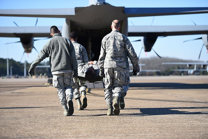 Airmen from the 19th Medical Group litter-carry a simulated patient onto a C-130J during an aeromedical evacuation training mission at Little Rock Air Force Base in 2019. (U.S. Air Force photo)