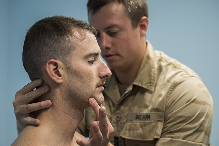 Belgian Medical Component 1st Lt. Olivier, a physical therapist, adjusts the neck of a pilot from the 332nd Air Expeditionary Wing, June 22, 2017, in Southwest Asia. Aircrew from the 332nd AEW received treatment for pains associated with flying high performance aircraft through a partnership program with the Belgian Medical Component. (U.S. Air Force photo/Senior Airman Damon Kasberg)