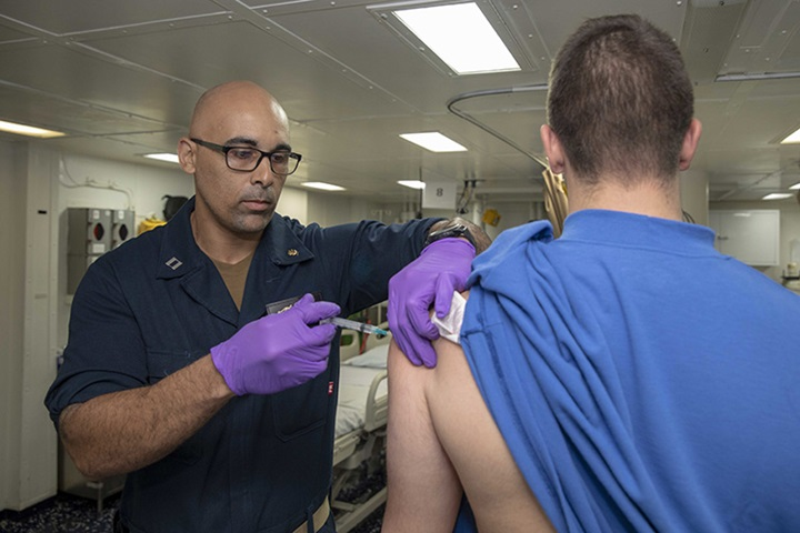 NORFOLK (Oct. 15, 2019) Lt. Sipriano Marte administers an influenza vaccination to Airman Tyler French in the intensive care unit aboard the Wasp-class amphibious assault ship USS Kearsarge (LHD 3). Kearsarge is underway conducting routine training. (U.S. Navy photo by Mass Communication Specialist Petty Officer 3rd Class Jacob Vermeulen/Released)