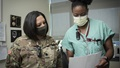 Military health personnel wearing face mask reviewing a patient's record