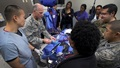 Military personnel sitting around a table, exhibiting medical items