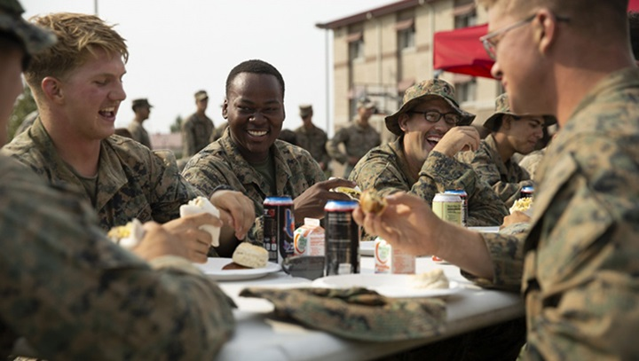 Picture of military personnel sitting at a table eating food together