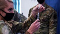 Military personnel administering the COVID-19 vaccine