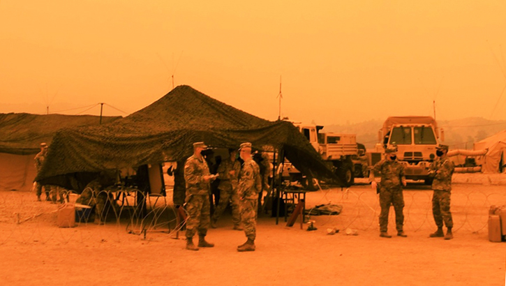 Picture of a military tent; an orange, smoky hue surrounds the tent and soldiers