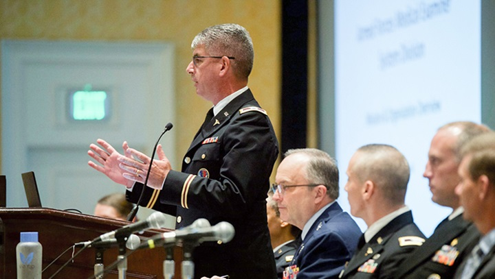 Military personnel speaking in front of an audience at the Military Health Systems Research Symposium