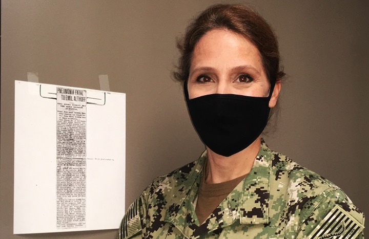 Image of Navy captain, wearing a mask, standing next to a piece of paper on the wall