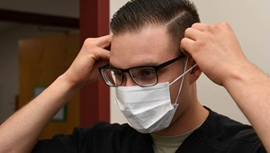 A dental assistant with the 319th Medical Group, demonstrates proper sanitary procedure by putting on a face mask at the medical treatment facility on Grand Forks Air Force Base, N.D.