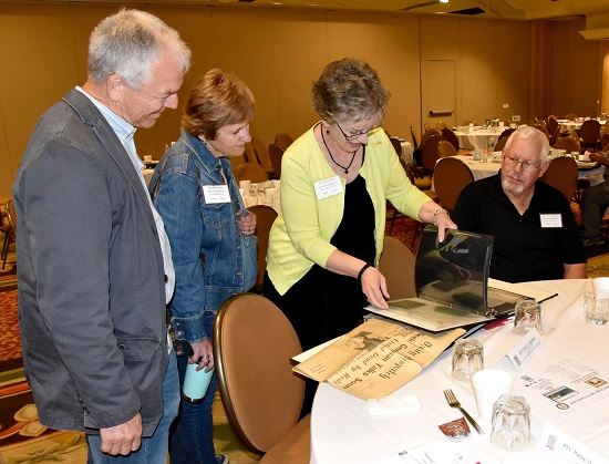 Mrs. Marjorie Mahar (center), shows relatives of missing service members photos and articles of her older brother, U.S. Army Private First Class Roland L. Bowser during a POW/MIA Accounting Agency Family Member Update in Louisville, Kentucky. Four of Mahar's five brothers served in the U.S. Armed Forces. (U.S. Air Force photo by Tech. Sgt. Robert M. Trujillo)