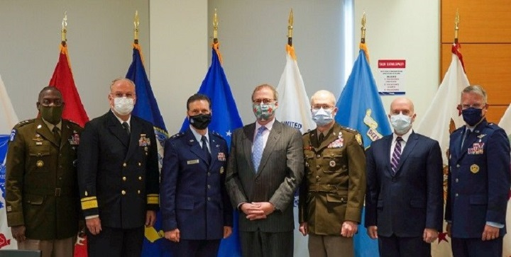 Military personnel, wearing masks, standing in a line in front of flags