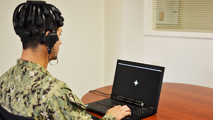 Soldier sitting in front of a laptop with headphones on