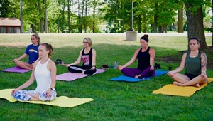 Five people sitting on yoga mats outside in the grass