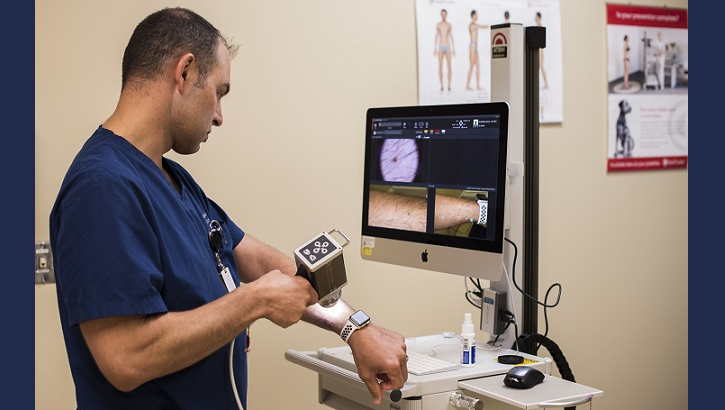 Air Force Maj. Thomas Beachkofsky, 6th Health Care Operations Squadron dermatologist, uses a body scanner microscope to take a picture of a spot on his arm at MacDill Air Force Base, Florida. A new software upgrade allows a complex algorithm to analyze an image captured with a camera and rate the severity of the spot for a dermatologist to review. (U.S. Air Force photo by Senior Airman Adam R. Shanks)