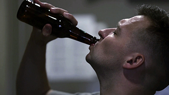 A man drinking beer from a bottle