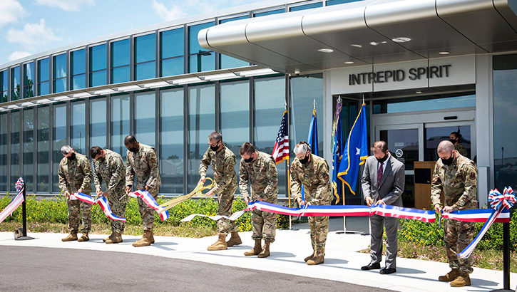 Soldiers holding a long ribbon and cutting it