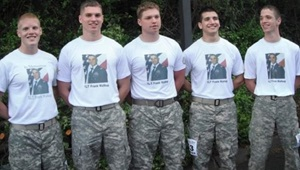 Five young men standing in a line, wearing the same t-shirt and pants