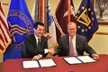 Dr. Scott Gottlieb, FDA Commissioner (left) and Mr. Thomas McCaffery, Principal Deputy Assistant Secretary of Defense (Health Affairs) (right), congratulate on another following the signing of a memorandum of understanding between the DoD and the FDA.  The ceremony acknowledges the existing partnership and the future collaboration on accessing life-saving medical products for U.S. troops on the battlefield.