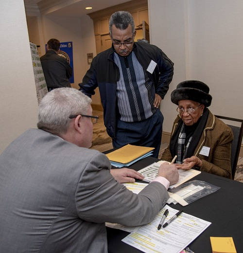 Dr. Tim McMahon (left), Armed Forces Medical Examiner System Department of Defense DNA Operations director, talks with Dorothy Britt, about family reference sample to see if she is eligible to donate DNA during a family member update in Birmingham, Alabama. The Defense POW/MIA Accounting Agency conducts periodic and annual government briefings for families of service members who are missing in action. These events are designed to keep family members informed of those still missing and to discuss in detail the latest information available about their specific case. (U.S. Air Force photo by Staff Sgt. Nicole Leidholm)