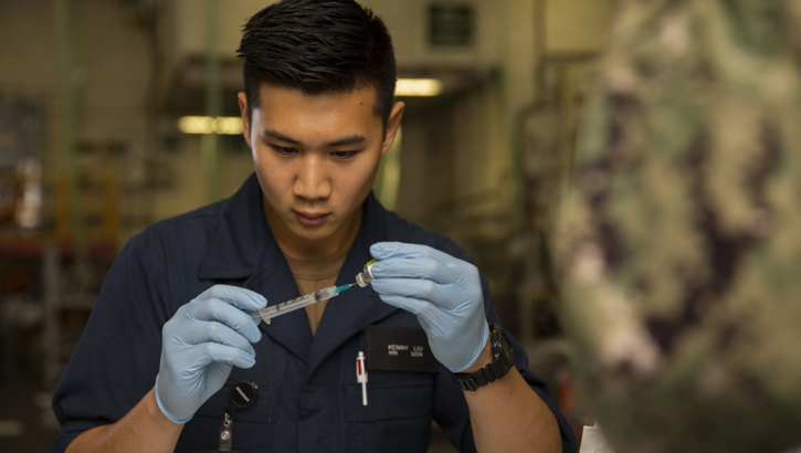 Navy Hospital Corpsman Kenny Liu, from San Jose, assigned to USS Gerald R. Ford's medical department, prepares a needle with a flu vaccination in the ship's hangar bay. (U.S. Navy photo by Mass Communication Specialist Seaman Apprentice Angel Thuy Jaskuloski)