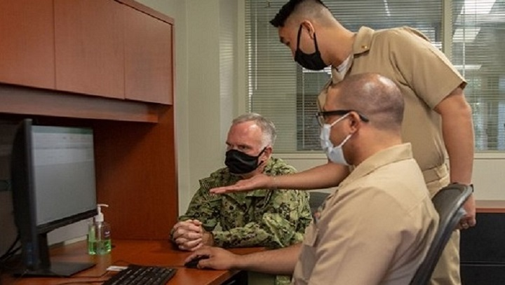 Three military personnel, wearing masks, in front of a computer screen