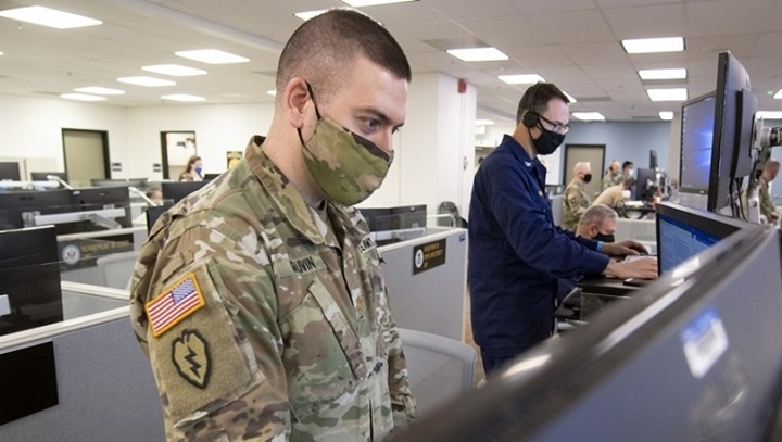 Soldier wearing mask, standing at computer monitors in an office building