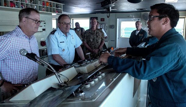 U.S. Military Sealift Command Cmdr. Andrew Chen, chief mate aboard the hospital ship USNS Comfort, (right), gives U.S. Air Force Maj. Gen. Lee E. Payne, (center), assistant director for Combat Support, Defense Health Agency, and Tom McCaffery, assistant secretary of Defense for Health Affairs, a tour of the ship while off the coast of Port-Au-Prince, Haiti. Comfort is working with health and government partners in Central America, South America, and the Caribbean to provide care on the ship and at land-based medical sites, helping to relieve pressure on national medical systems, including those strained by an increase in cross-border migrants. (U.S. Navy photo by Mass Communication Specialist Seaman Jordan R. Bair)