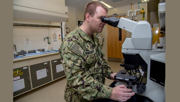 Navy Petty Officer 2nd Class Tyler Wiedmeyer, Armed Forces Medical Examiner System histotechnichian, looks at slides of tissues under a microscope before handing them off to a medical examiner June 6, 2019. The stained tissues help medical examiners see down to the cellular level for a diagnosis of cause of death. (U.S. Air Force photo by Staff Sgt. Nicole Leidholm)