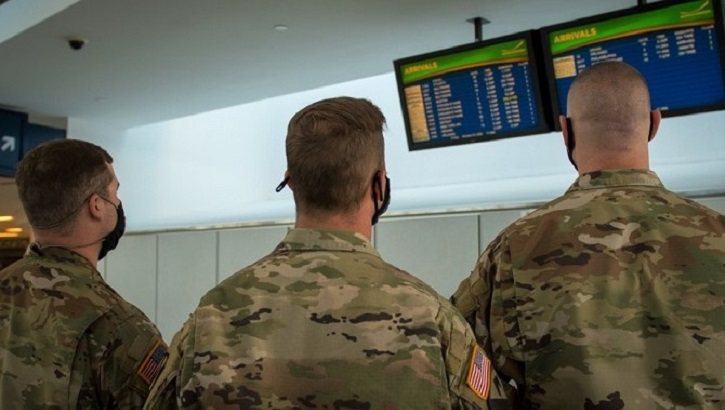 Soldiers wearing masks, looking at flight information in airport