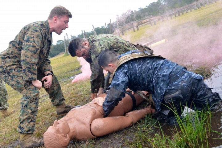Hospital Corpsman 2nd Class Kyle Hamlin, an instructor for the hospital corpsman trauma training program at Naval Hospital Jacksonville, helps motivate sailors during a Tactical Combat Casualty Care course. (U.S. Navy photo by Jacob Sippel)