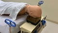 Image of a dummy laying face-down on a hospital bed