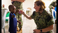 Navy Cmdr. Sara Naczas, a nurse assigned to the hospital ship USNS Comfort, helps a boy roll his yo-yo at a temporary medical treatment site in Kingston, Jamaica. Comfort is working with health and government partners in Central America, South America, and the Caribbean to provide care on the ship and at a temporary medical treatment site, helping to relieve pressure on national medical systems, including those strained by an increase in cross-border migrants. (U.S. Navy Photo by Mass Communication Specialist 3rd Class Maria G. Llanos)