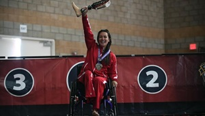 Woman in wheelchair on podium; holding up prosthetic leg
