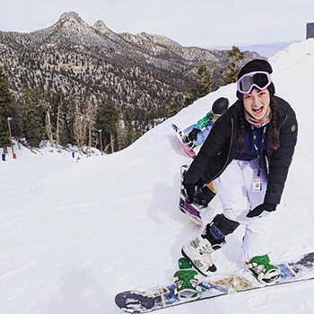 Woman snowboarding with a brace on her knee