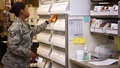 A military pharmacist choosing medication from a shelf
